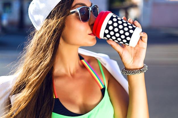 Giovane donna con berretto e sunglasess bere caffè in strada