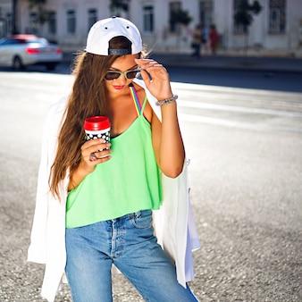 Giovane donna con cappello e occhiali da sole, t-shirt verde e jeans che beve caffè in strada