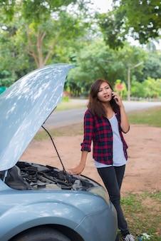 Молодая женщина с автомобилем ломается, и она звонит в аварийную службу.