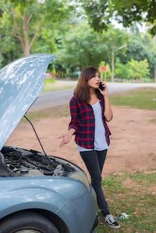 Giovane donna con auto si rompe e lei sta chiamando i servizi di emergenza.