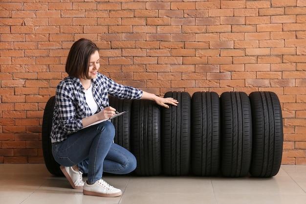 자동차 타이어와 클립 보드 벽돌 벽 근처 젊은 여자