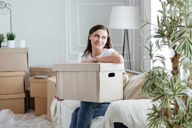 Young woman with a cardboard box sitting on the sofa