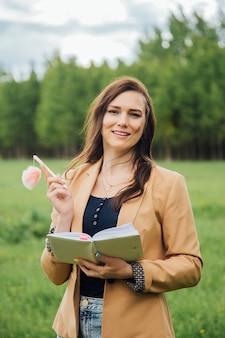 Молодая женщина в повседневной одежде пишет в дневнике на фоне природы