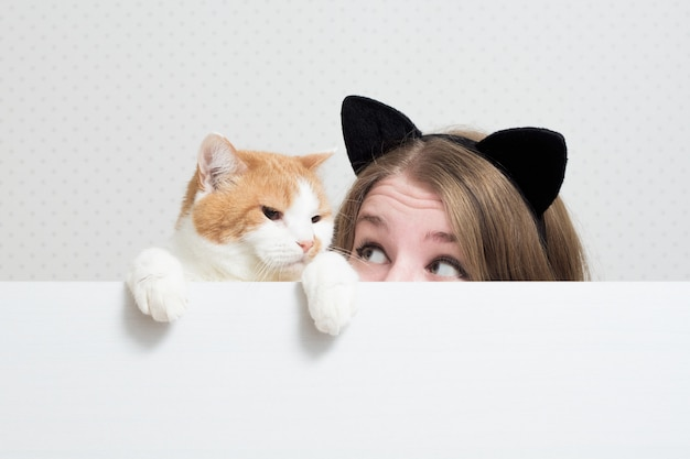 고양이와 젊은 여자는 흰색 배너 뒤에 숨어 서로보고