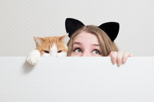 고양이와 젊은 여자는 흰색 배너 뒤에 숨어