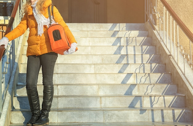 Young woman with cat in carrier bag on stairs