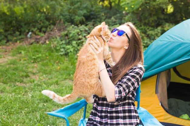 テントの近くに猫と若い女性