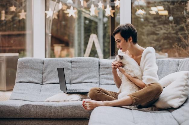 Молодая женщина с кошкой работает на ноутбуке из дома