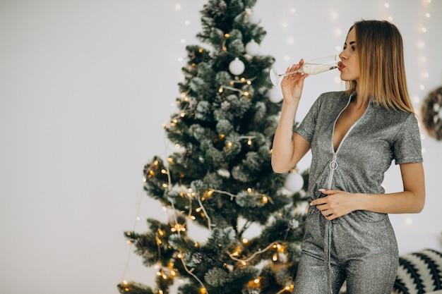 クリスマスツリーのシャンペーンを持つ若い女性
