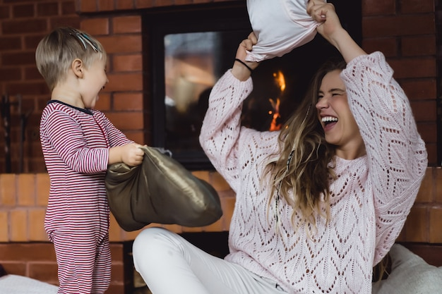 Young woman with a child. mom and son are fooling around, having fun near the fireplace.