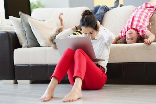 그녀의 무릎에 노트북과 함께 바닥에 앉아 그녀의 귀를 덮고 아이들과 젊은 여자