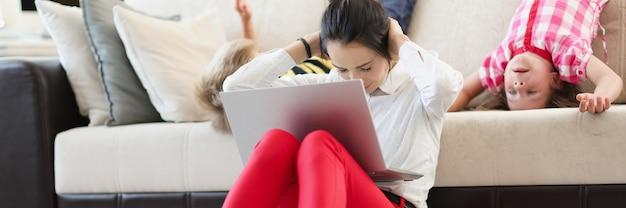 그녀의 무릎에 노트북과 그녀의 귀를 덮고 바닥에 앉아 아이들과 함께 젊은 여자
