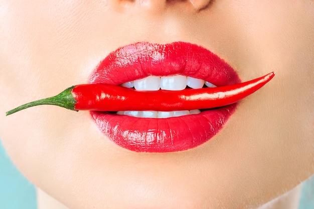 Молодая женщина с красным перцем чили, изолированным синим цветом.