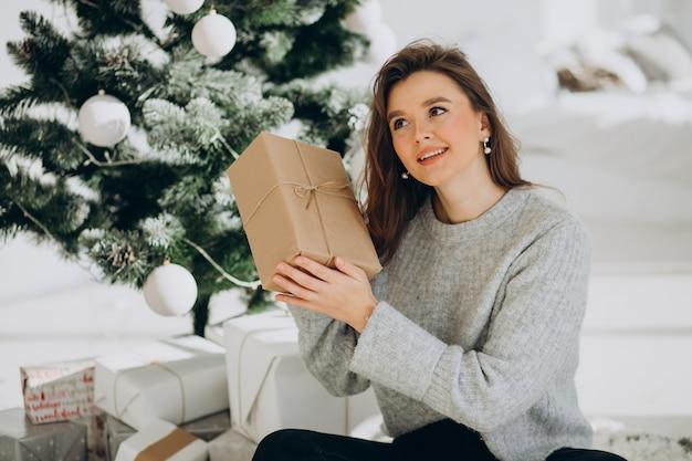 Giovane donna con regali di natale dall'albero di natale