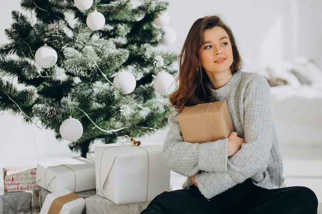Young woman with christmas presents by the christmas tree