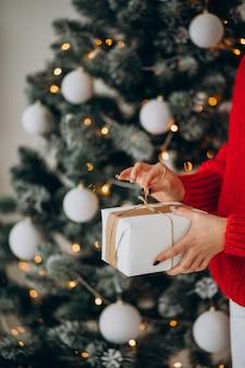 Молодая женщина с рождественскими подарками у елки