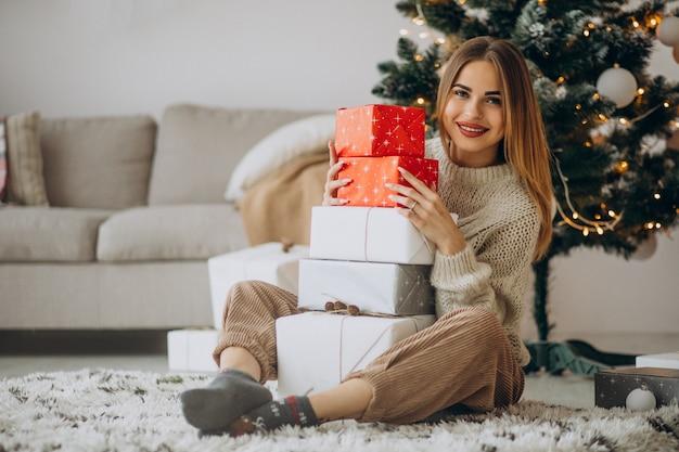 クリスマスツリーでクリスマスプレゼントと若い女性