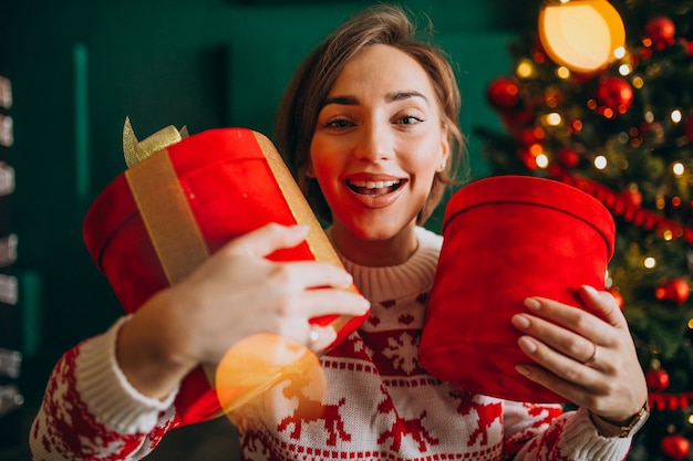 Young woman with christmas tree holding red boxes