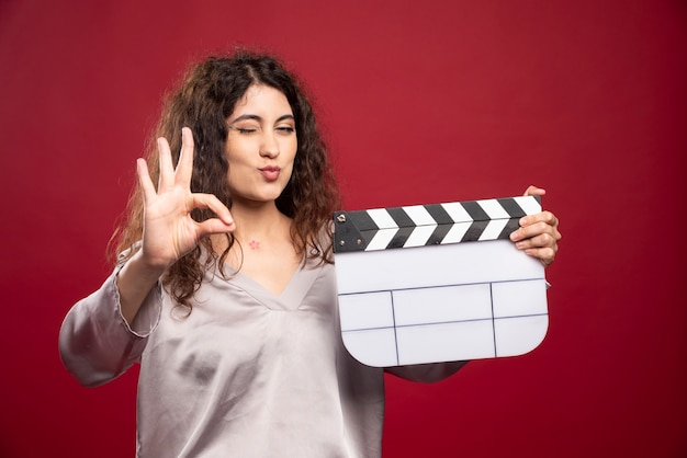Young woman with clapperboard giving sign.