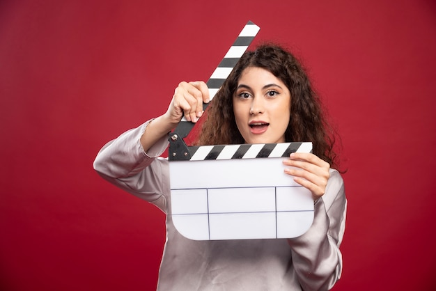Young woman with clapperboard standing.