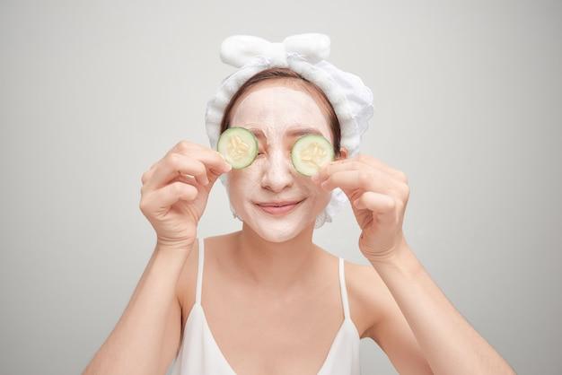 白い背景で隔離のキュウリのスライスを保持している粘土の顔のマスクを持つ若い女性