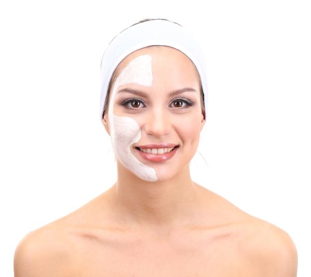 Молодая женщина с глиняной маской для лица, изолированной на белом