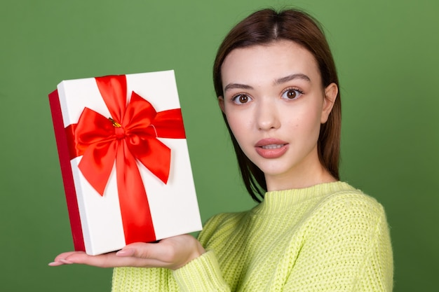 Young woman with clean perfect natural skin and makeup brown big lips on green wall holds gift box happy excited