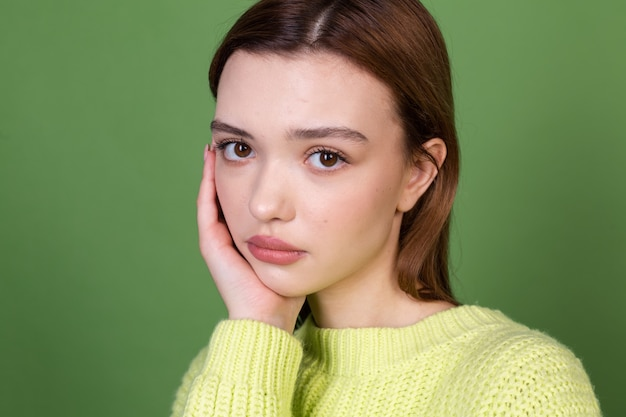 Young woman with clean perfect natural skin and makeup brown big lips on green wall unhappy sad disappointed