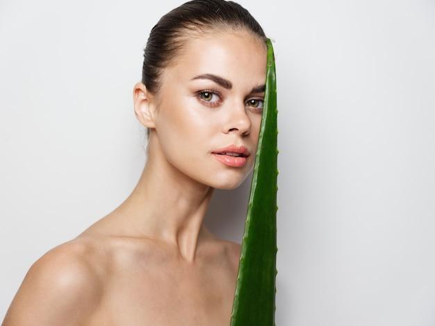 手にアロエの葉を持ってきれいな肌と裸の肩を持つ若い女性