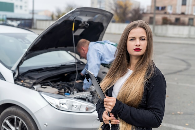 Young woman with clipboard and worker repairing car