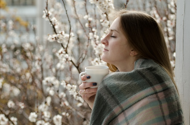Young woman with closed eyes and a cup of tea enjoying the spring