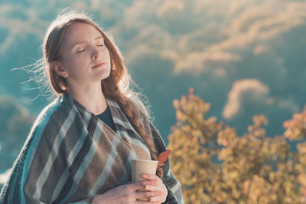 Молодая женщина с закрытыми глазами наслаждается воздухом. бумажный стаканчик в руках, солнечный день