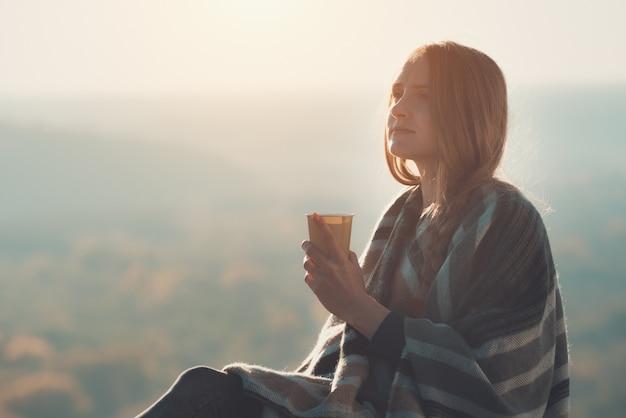 Молодая женщина с закрытыми глазами наслаждается воздухом