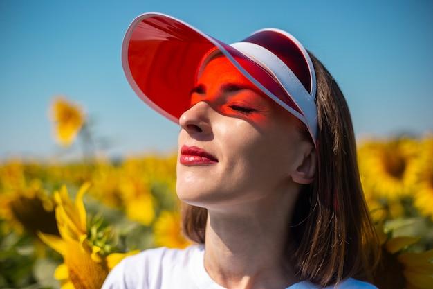 赤いサンバイザーと白いtシャツで目を閉じて空を見ている若い女性
