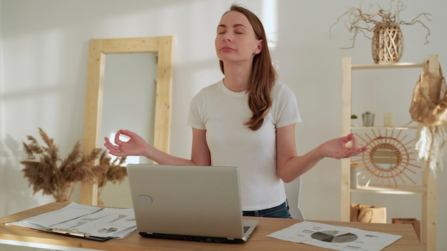 Young woman with closed eyes meditation spread hands in yoga pose sit after work at desk with laptop