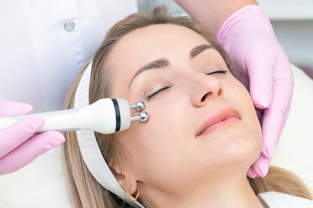 Young woman with closed eyes receiving rf lifting procedure in beauty salon.