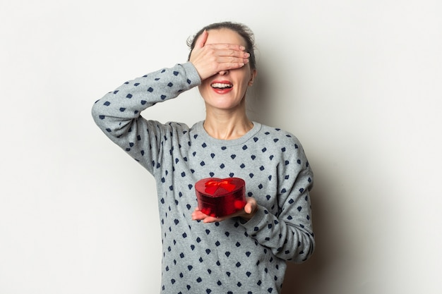 Young woman with closed eyes rejoices at the gift on a light background. valentine's day, birthday. banner.