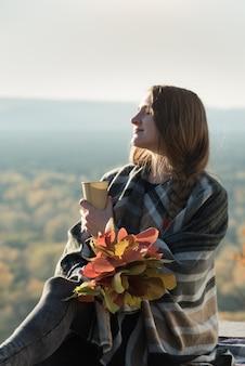 Молодая женщина с закрытыми глазами сидит на холме. бумажный стаканчик в руках и букет из желтых листьев. наслаждаясь солнечным днем