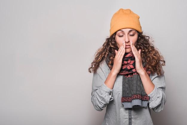 Giovane donna con gli occhi chiusi che soffrono da freddo contro fondo grigio