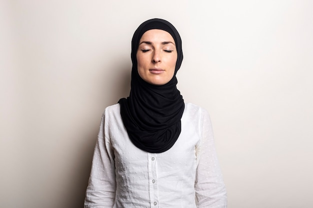 Young woman with closed eyes in white shirt and hijab