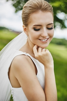 A young woman with closed eyes and with elegant wedding coiffure smiling and posing outdoors