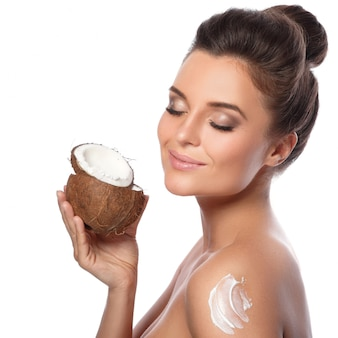 Young woman with a coconut and moisturizing cream on her shoulder