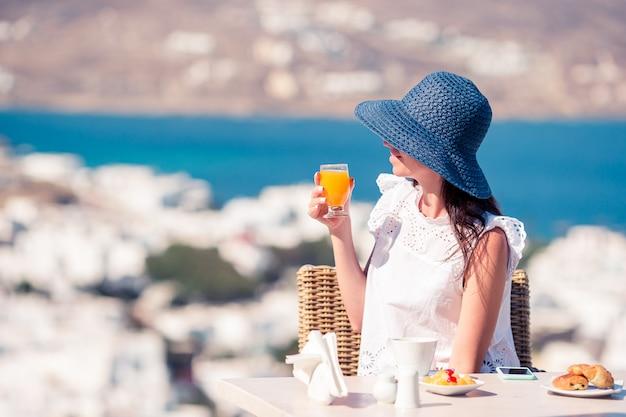 ミコノスの街の素晴らしい景色と屋外カフェでコーヒーを持つ若い女性。