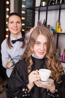 Young woman with coffee cup and hairdresser holding hairspray.