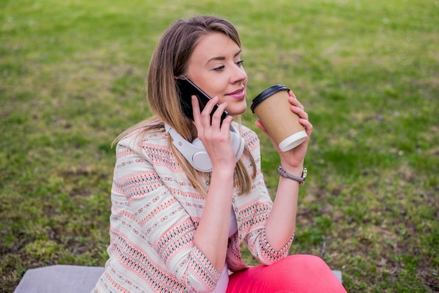 Young woman with coffee to go in hand using a mobile phone and headphones in the park. young stylish beautiful girl listening to music, mobile phone,headphones, enjoying, smiling, happy, cool accessories, vintage style, having fun, laughing, park