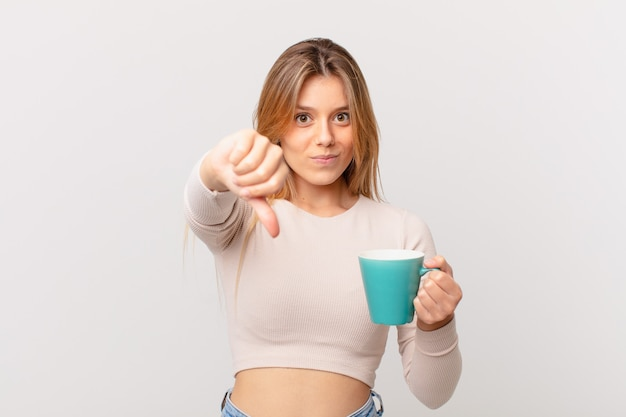 Young woman with a coffee mug feeling cross,showing thumbs down