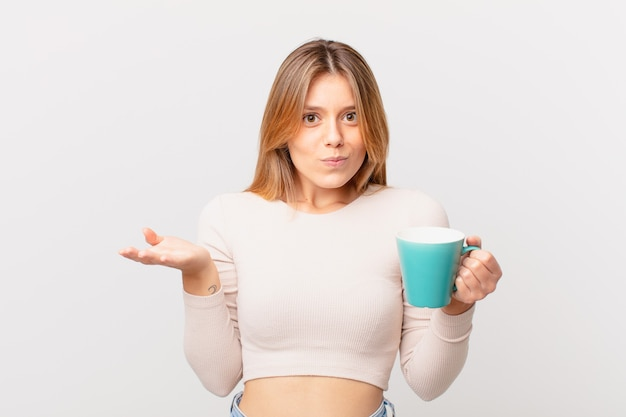 Young woman with a coffee mug feeling puzzled and confused and doubting