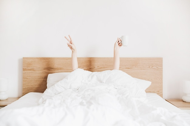 화이트 리넨과 침대에 커피 잔과 젊은 여자