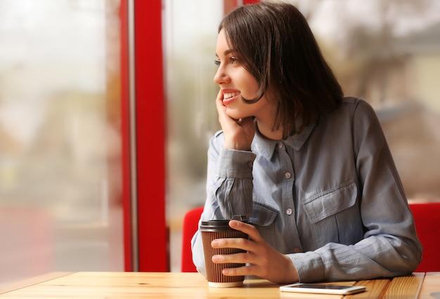 Молодая женщина с кофе, сидя в кафе