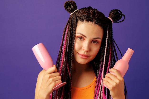 Молодая женщина с красочными афро-косами держит бутылку напитка на фиолетовом фоне